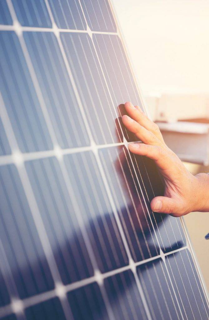 Close up of engineer hand is checking an operation of sun and cleanliness of photovoltaic solar panels on a sunset. Concept: renewable energy, technology,electricity,service, green,future